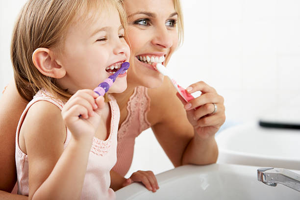mother and daughter brushing teeth together - teeth stock photos and pictures