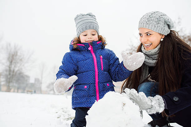 mother and daughter building a snowman in winter nature - schneemann bauen stock-fotos und bilder