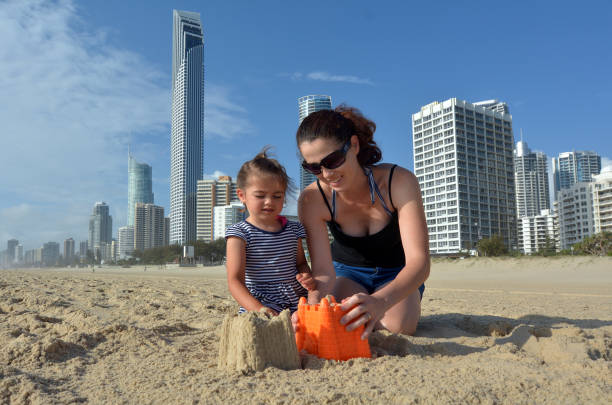 Mother and daughter builds sand castle in Surfers Paradise Australia stock photo