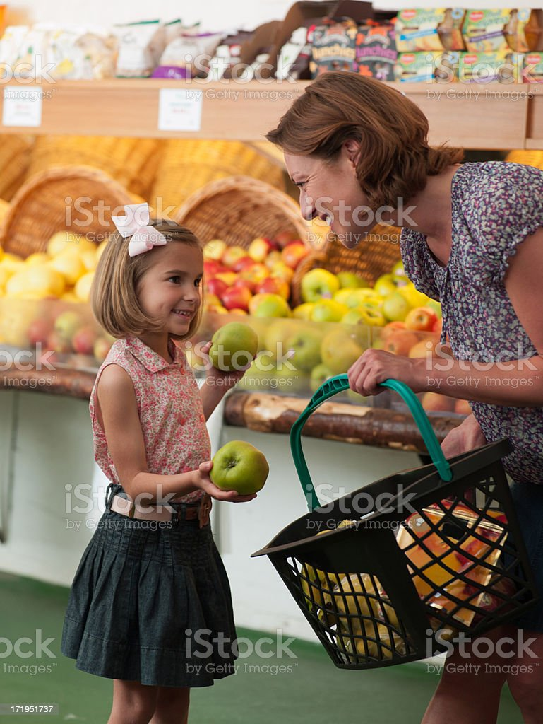 Mother and daughter buying fruit in grocery store royalty-free stock photo