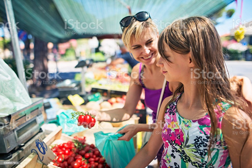Mother and daughter buying tomatoes at the Italian farmer's market stock photo
