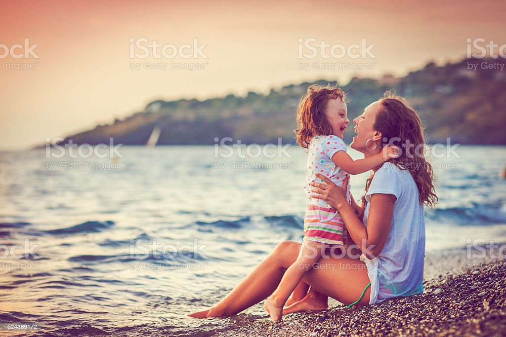 Mother and daughter by the sea stock photo