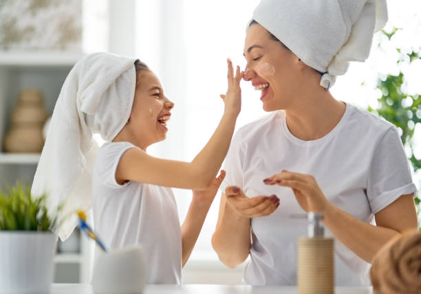 Mother and daughter caring for skin stock photo