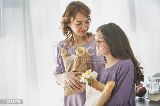 Woman and her daughter are done with grocery shopping. They are carrying paper bags with fresh bread, fruit and flowers.