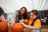 Mother and daughter carving pumpkins at a farm after picking them in preparation for Halloween.