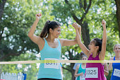 Mid adult Asian American woman and her elementary age daughter are holding hands and celebrating as they cross the finish line during a marathon. Parent and child are competing in race for charity.
