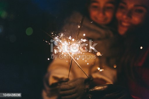 Mother and daughter with burning sparklers outside