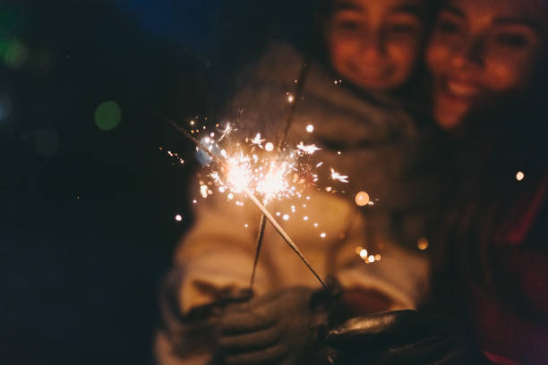 mother and daughter celebrating christmas - sparkler stock pictures, royalty-free photos & images