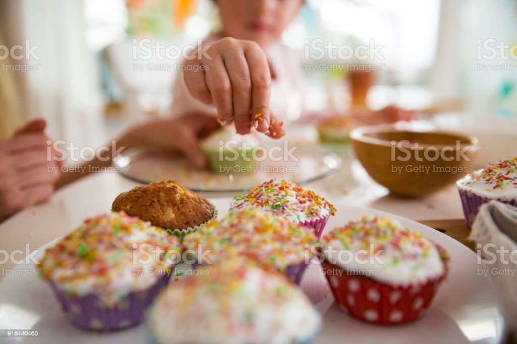 Mother and daughter celebrating Easter, cooking cupcakes, covering with glaze. Happy family holiday. Cute little girl in bunny ears. stock photo