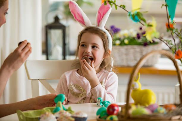 mutter und tochter feiert ostern schokoladeneier zu essen. glücklichen familienurlaub. niedliche kleine mädchen in hasenohren lachen, lächeln und spaß haben. - kinderschokolade stock-fotos und bilder
