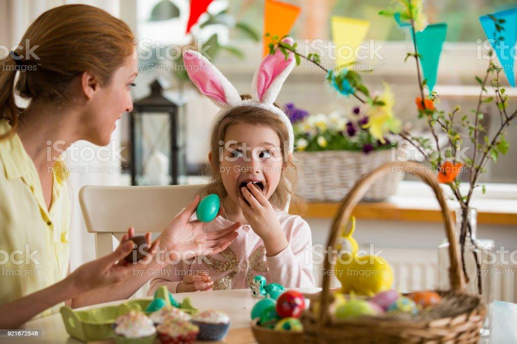Mutter und Tochter feiert Ostern Schokoladeneier zu essen. Glücklichen Familienurlaub. Niedliche kleine Mädchen in Hasenohren lachen, Lächeln und Spaß haben. – Foto