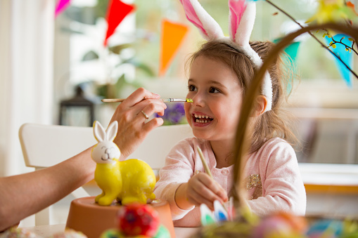 A mother and daughter celebrating Easter, painting bunny with brush in yellow color. Happy family smiling and laughing. Cute little girl in bunny ears preparing the holiday.