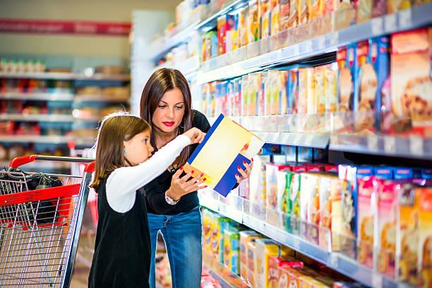 mutter und tochter, die lebensmittel im supermarkt etikettieren - kinder verpackung stock-fotos und bilder