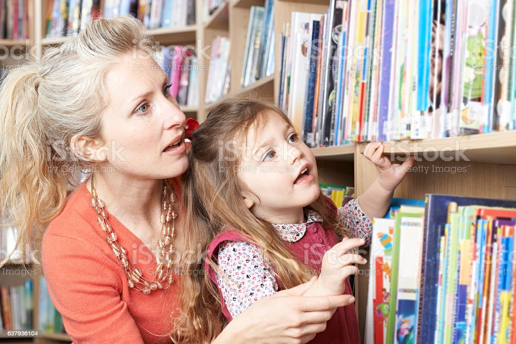 Mother And Daughter Choosing Book From Library Shelf