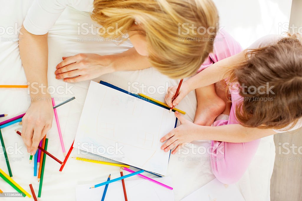 Mother and daughter coloring in bedroom. stock photo