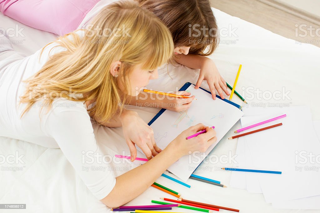 Mother and daughter coloring in bedroom stock photo
