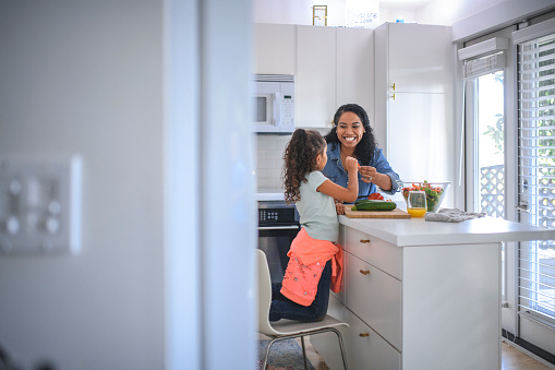 Smiling mother cutting bell pepper at kitchen island. Woman and daughter preparing food together at home. They are representing healthy lifestyle.
