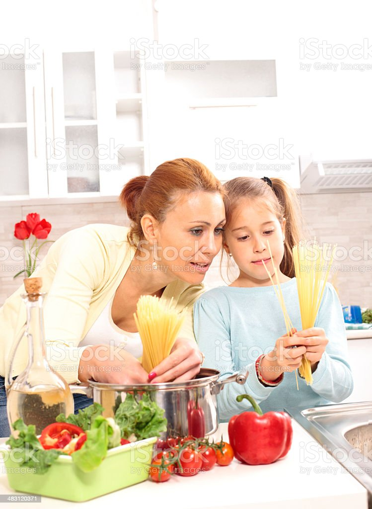 Mother and daughter cooking in kitchen royalty-free stock photo