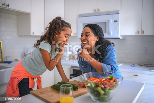 Smiling mother and daughter tasting vegetables at kitchen island. Woman and daughter preparing food together at home. They are representing healthy lifestyle.