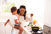 Mother and daughter cooking the soup at the kitchen. The woman holding child and tasting a bouillon with a wooden spoon. Daughter and mother bonding, healthy meal, lifestyle, and culinary concepts.