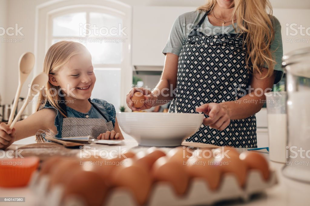 Mother and daughter cooking together in kitchen stock photo