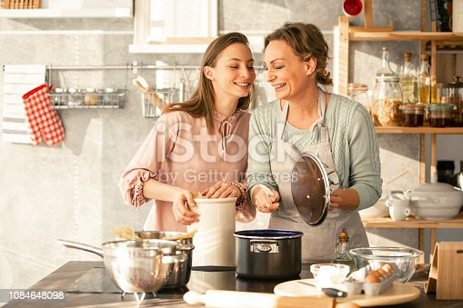 istock Mother and daughter cooking together 1084648098