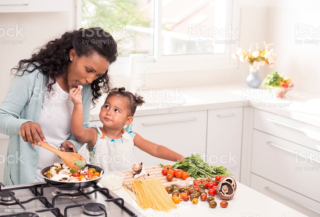 Mother and daughter cooking together. stock photo