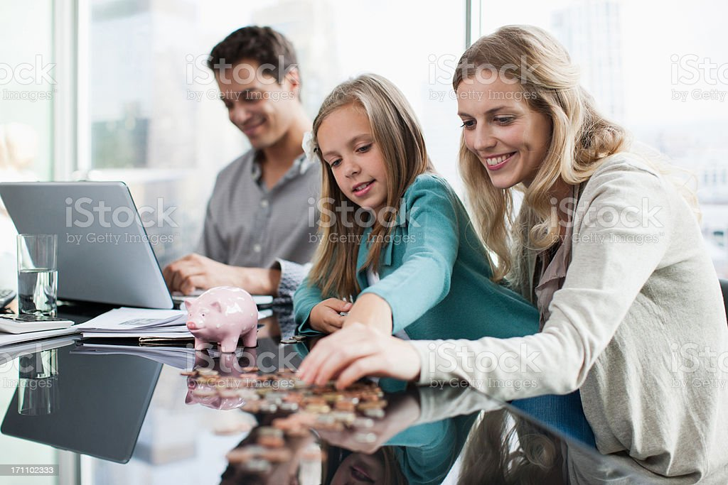 Mother and daughter counting coins stock photo