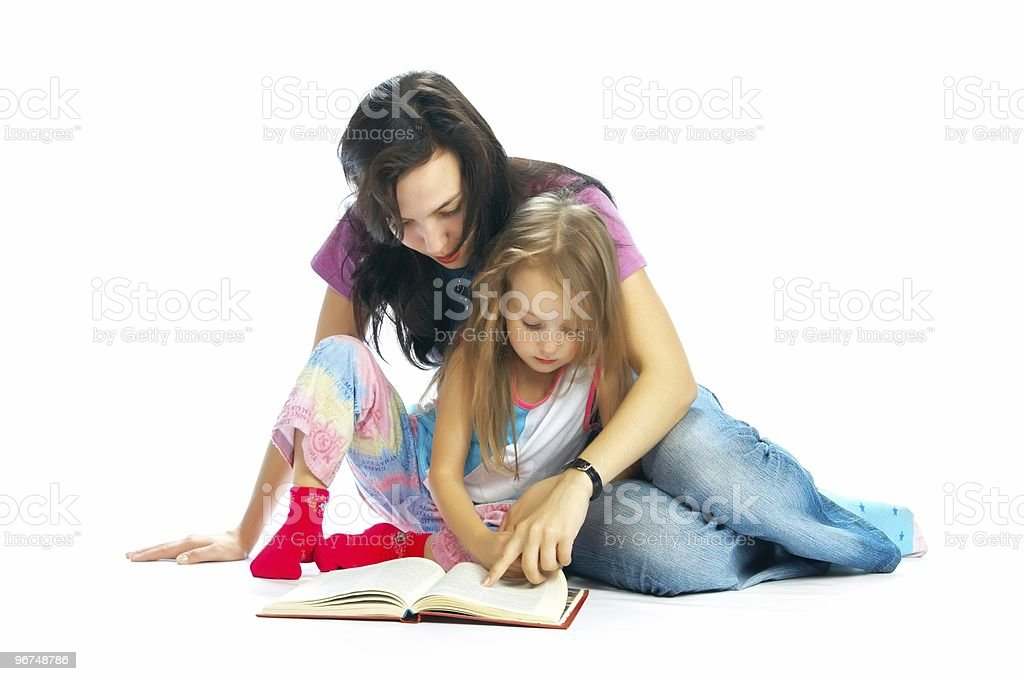 Mother and daughter cuddling and reading a book together royalty-free stock photo