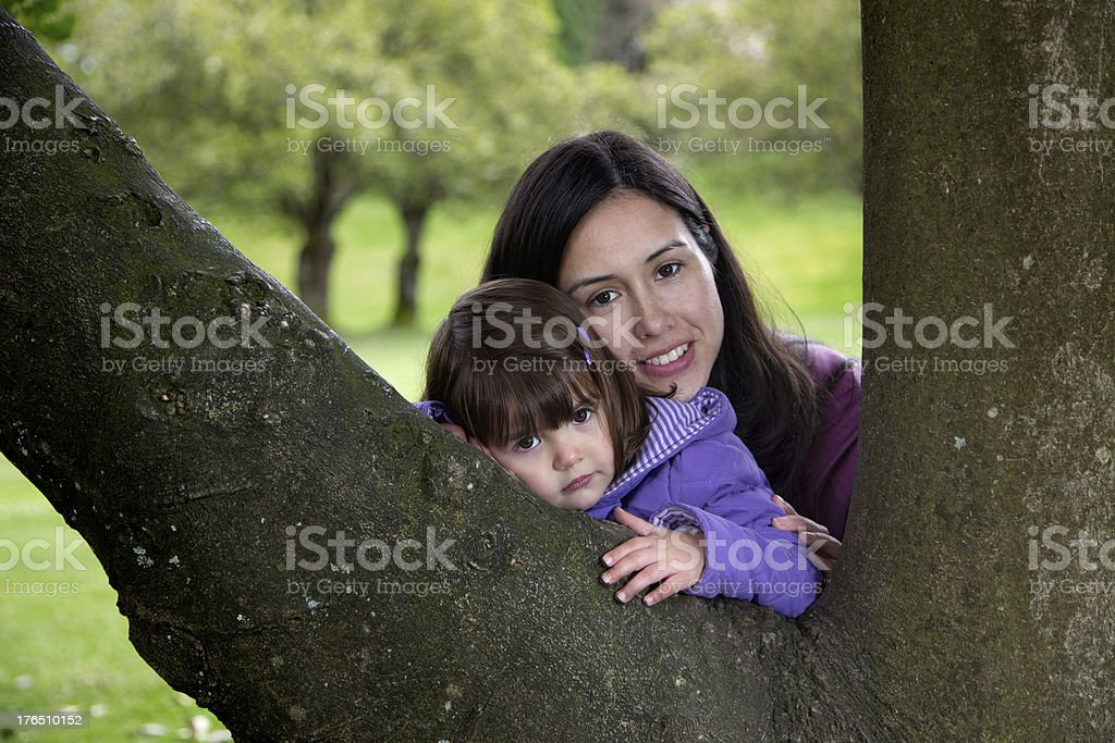 Mother and Daughter Cuddling as they Rest on a Tree stock photo