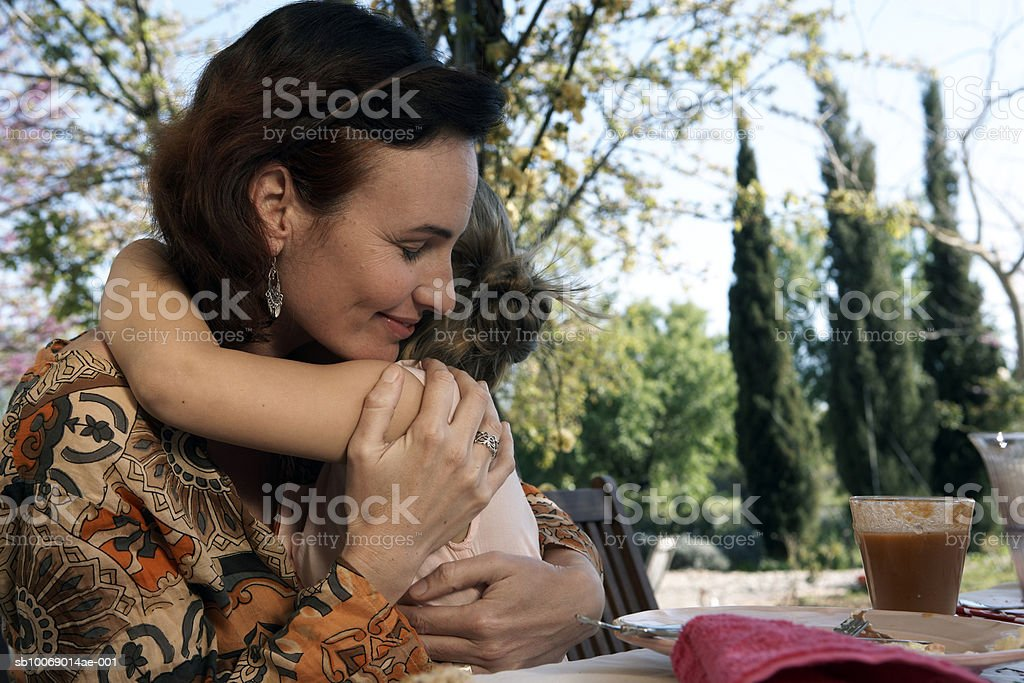 Mother and daughter (8-9) cuddling royalty-free stock photo