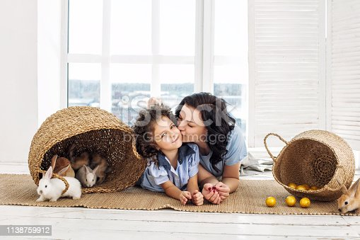 istock Mother and daughter cute beautiful and happy with rabbits and Easter eggs in wicker baskets together 1138759912