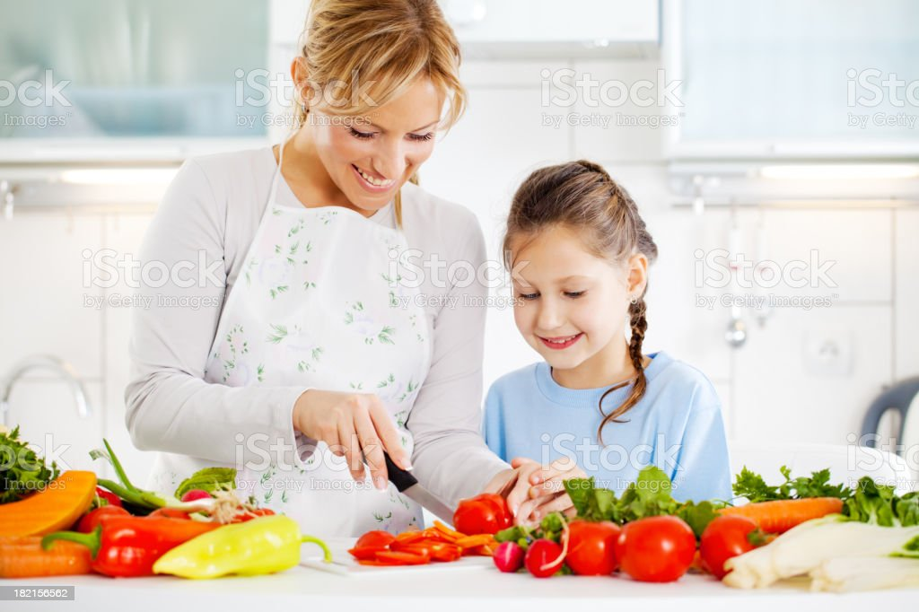 Mother and daughter cutting vegetables in the kitchen. royalty-free stock photo