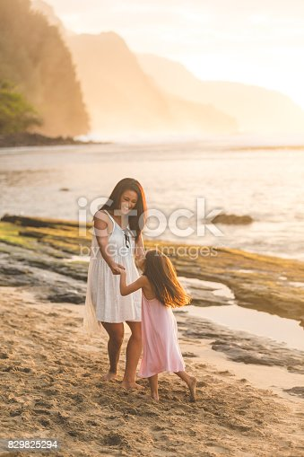 istock Mother and daughter dance and play in the sand together 829825294