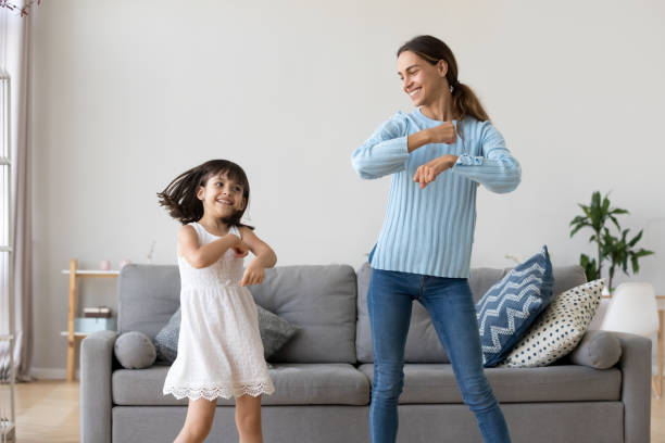Mother and daughter dancing together in living room Cheerful mother little daughter standing in living room at home moving dancing to favourite song together. Child have fun with elder sister nanny or loving mother active leisure and lifestyle concept dancing stock pictures, royalty-free photos & images