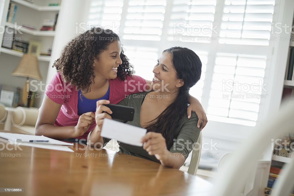 Mother And Daughter Depositing Check Through Mobile Phone royalty-free stock photo