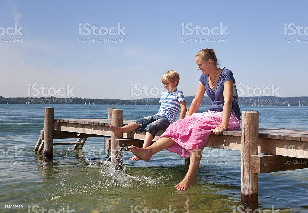 Mother and daughter dipping feet in lake stock photo