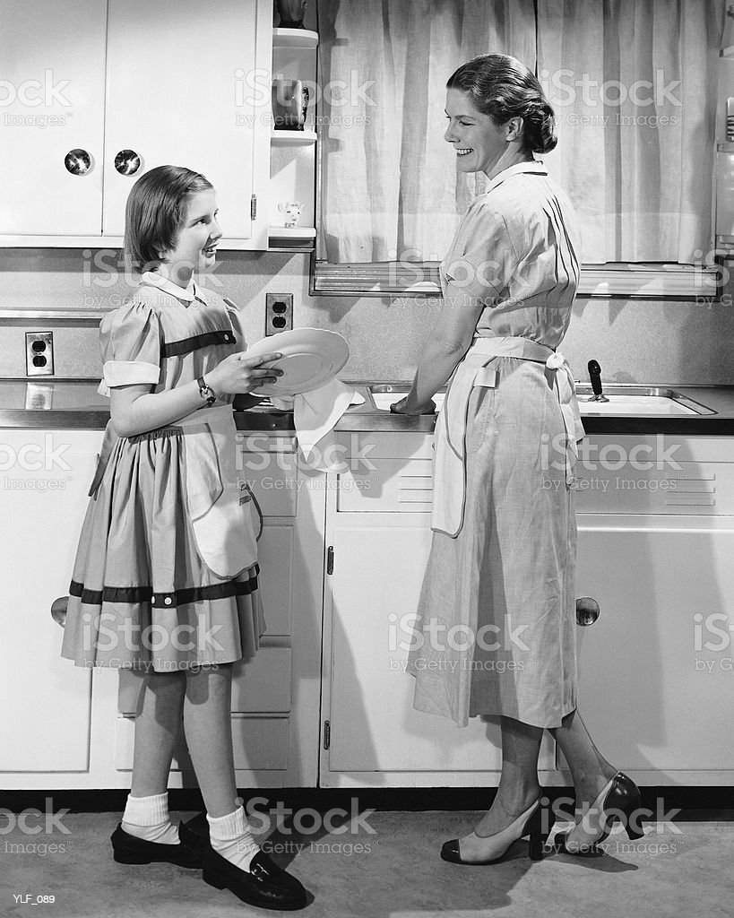 Mother and daughter doing dishes royalty-free stock photo