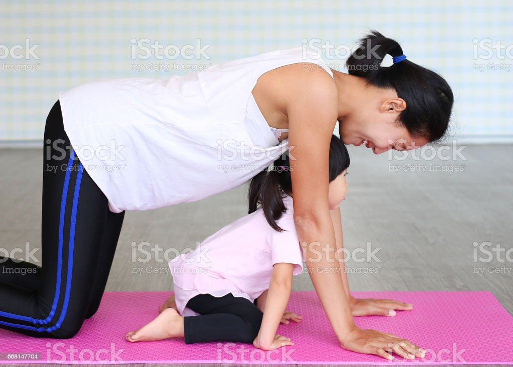 Mother and daughter doing exercise stock photo