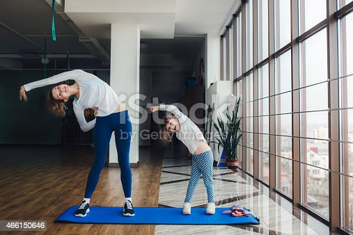 istock Mother and daughter doing yoga at home 466150646