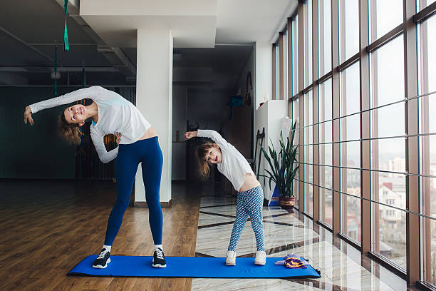 Mother and daughter doing yoga at home stock photo