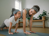 istock Mother and daughter doing yoga 1221256351
