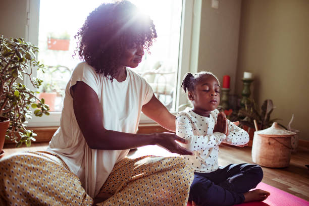 mother and daughter doing yoga - meditation stock pictures, royalty-free photos & images