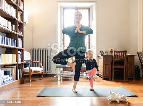 mother and little daughter practicing yoga together at home