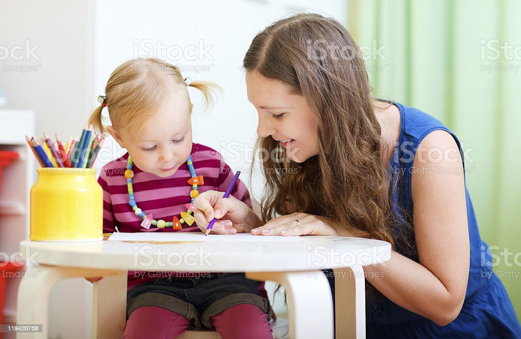Mother and daughter drawing at a kids table stock photo