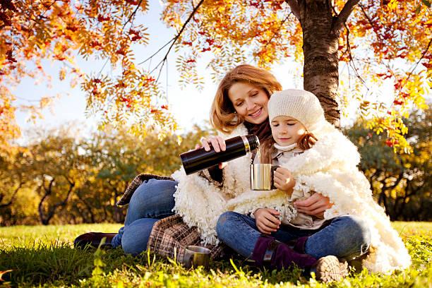Mutter und Tochter nach draußen und trinkt heißen Tee im Herbst Park – Foto