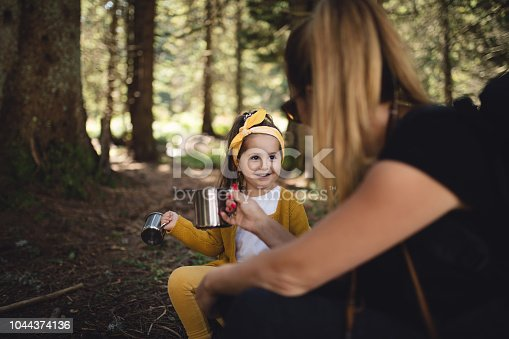 istock Mother and daughter drinking tea from a stainless steel mug in a forest 1044374136