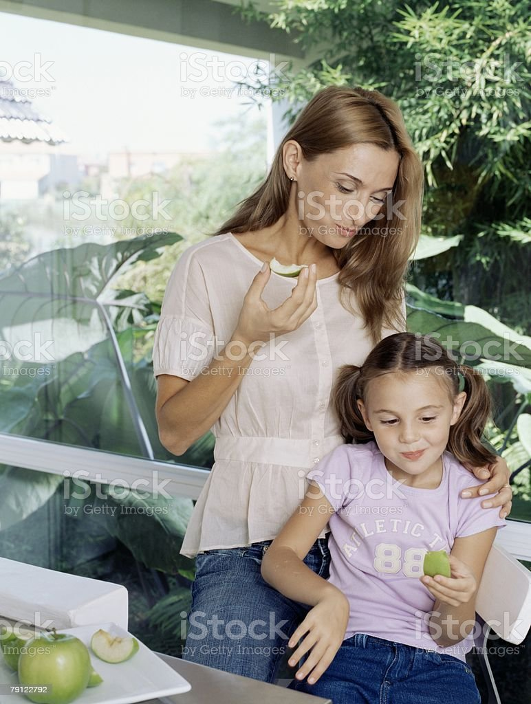 Mother and daughter eating apple slices royalty-free 스톡 사진