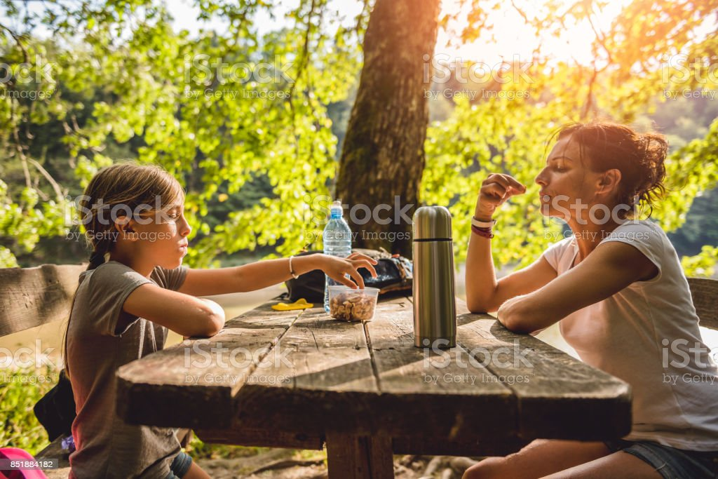 Mother and daughter eating at a picnic table stock photo