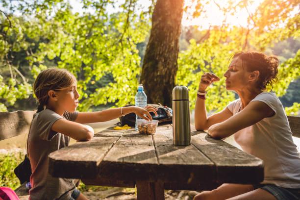 mutter und tochter bei einem picknick-tisch essen - nussbaumholz stock-fotos und bilder